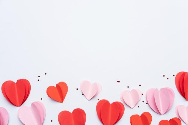 Papierherzen auf weißem hintergrund für eine glückliche valentinstag-grußkarte