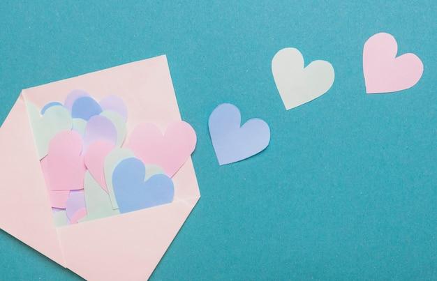Papierherzen der verschiedenen farbe verstreut vom weißen umschlag über blauem hintergrund.