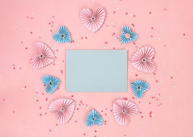 Papierherzen in scrapbooking-technik und rosa und rote süßigkeiten-zuckersüßigkeitsherzen fliegen auf dem lebenden korallenhintergrund heraus. valentinstag. liebeskonzept. platz für text. breites banner - bild.