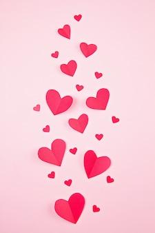 Papierherzen über dem rosa pastellhintergrund. abstrakter hintergrund mit papierschnittformen. sainte valentine, muttertag, geburtstagsgrußkarten, einladung, feierkonzept