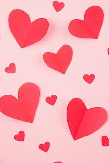 Papierherzen über dem rosa pastellhintergrund