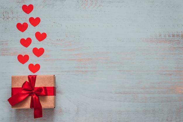Papierherzen und ein handwerksgeschenk mit rotem band auf einem hellen gemalten hölzernen hintergrund. seitenansicht von oben, flach gelegt. valentinstag konzept. copyspace.