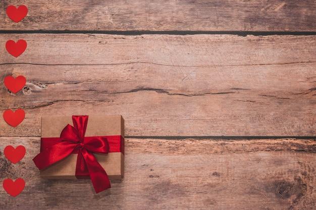 Papierherzen und ein handwerksgeschenk mit rotem band auf einem hölzernen hintergrund. seitenansicht von oben, flach gelegt. valentinstag konzept. copyspace.