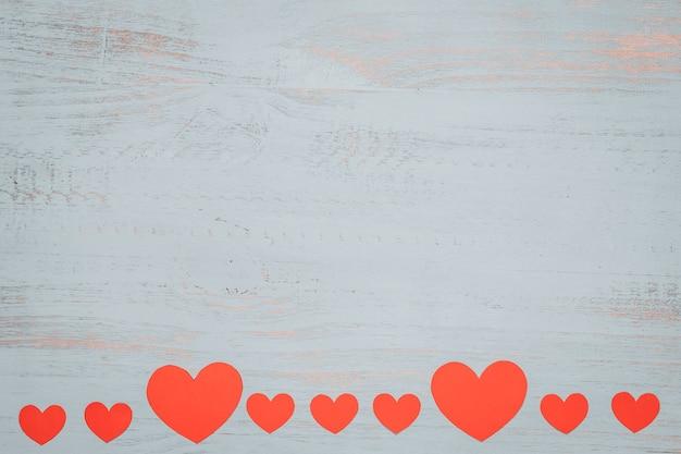 Papierherzen und ein weißes geschenk mit rotem band auf einem hellen gemalten hölzernen hintergrund. seitenansicht von oben, flach gelegt. valentinstag konzept. copyspace.