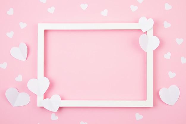 Papierherzen und weißer rahmen über dem rosa pastellhintergrund.