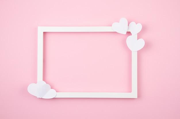 Papierherzen und weißer rahmen über dem rosa pastellhintergrund