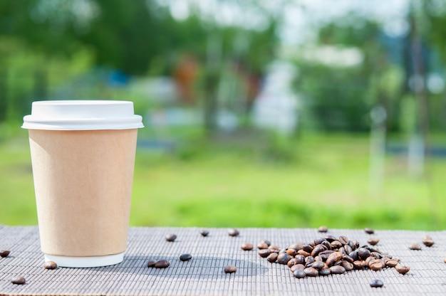 Papierkaffeetasse auf dem hintergrund der natur und der kaffeebohnen.