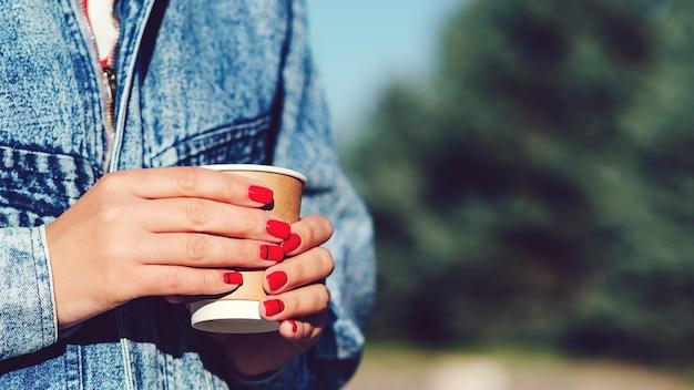 Papierkaffeetasse in frauenhänden mit perfekter maniküre. weibliche hand mit kaffee zum mitnehmen. frau, die tasse in den händen hält. kaffee zum mitnehmen trinken.