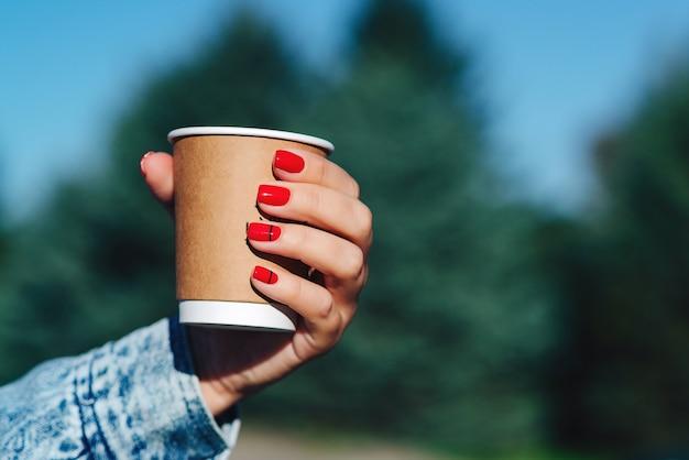 Papierkaffeetasse in frauenhänden mit perfekter maniküre. weibliche hand mit kaffee zum mitnehmen.