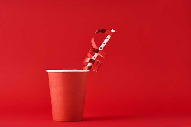 Papierkaffeetasse mit dekorationen und stroh auf rotem backgrond. valentinstag festliches konzept