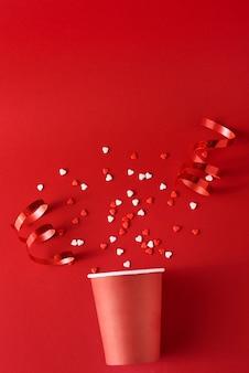 Papierkaffeetasse mit festlichen dekorationen und konfettis auf rotem backgrond, draufsichtebenenlage. kreatives minimalismuskonzept