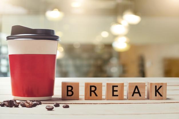 Papierkaffeetasse und break-holzbuchstabe mit unscharfer kaffeestube