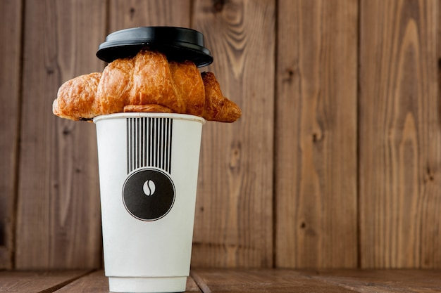 Papierkaffeetasse und croissants auf hölzernem hintergrund, kopierraum.