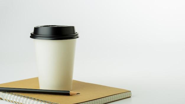 Papierkaffeetasse und ein notizbuch auf weißem schreibtischhintergrund mit kopienraum. - bürobedarf oder bildungskonzept.