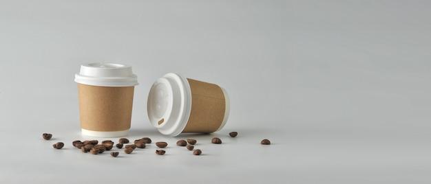 Papierkaffeetasse und kaffeebohnen auf weißem hintergrund.