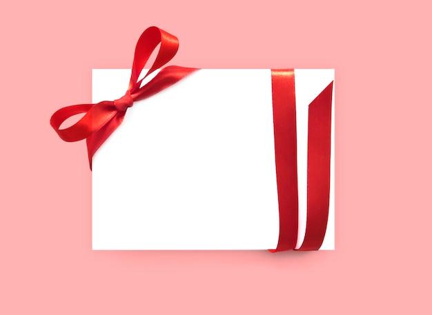 Papierkarte mit rotem schleifenband.