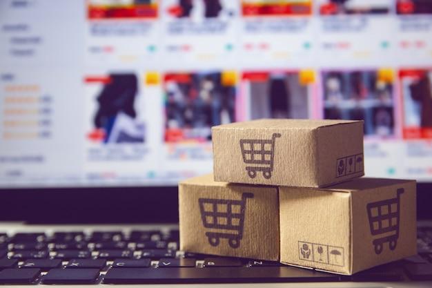 Papierkartons oder paket mit einem einkaufswagenlogo auf einer laptoptastatur