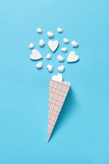 Papierkegel mit kleinen weißen gipsherzen als süßes eisdessert