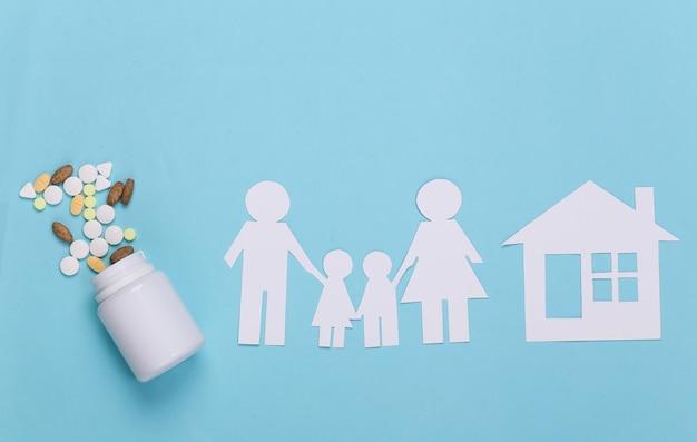 Papierkettenfamilie mit haus, flaschenpillen auf blau, krankenversicherungskonzept