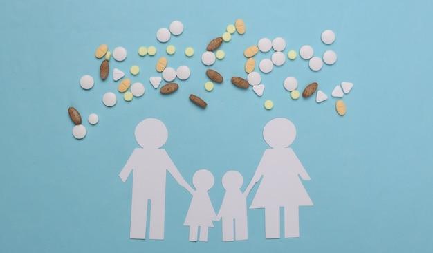 Papierkettenfamilie, pillen auf blau, krankenversicherungskonzept