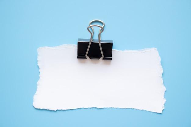 Papierklammer und reißende papieranmerkung über blauen hintergrund