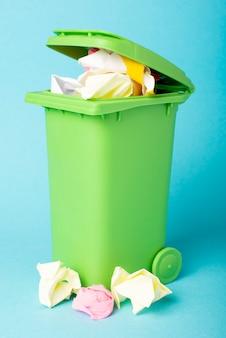 Papierkorb auf einem blauen hintergrund, gefüllt mit papier. papier. abfallrecycling.