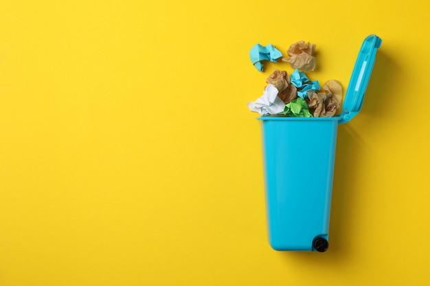 Papierkorb mit papierkorb auf gelbem hintergrund, platz für text