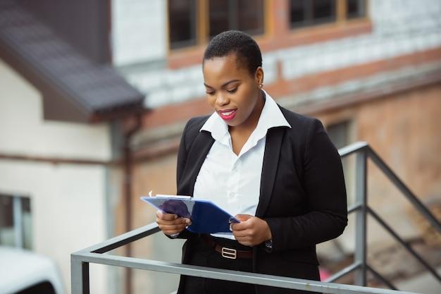 Papierkram. afroamerikanische geschäftsfrau in bürokleidung lächelnd, sieht selbstbewusst und glücklich aus, beschäftigt. konzept für finanzen, wirtschaft, gleichstellung und menschenrechte. schönes junges weibliches modell, erfolgreich.