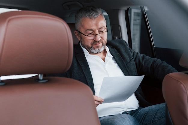 Papierkram auf dem rücksitz des autos. senior geschäftsmann mit dokumenten