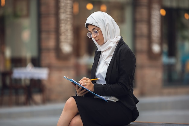 Papierkram. schönes muslimisches erfolgreiches geschäftsfrauenporträt, überzeugter glücklicher ceo, führer, chef oder manager. die verwendung von geräten, gadgets und die arbeit unterwegs sieht beschäftigt aus. charmant. inklusiv, vielfalt.