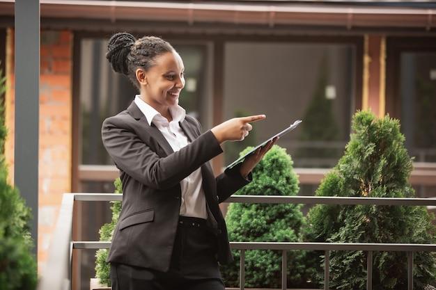 Papierkram, zeigend. afroamerikanische geschäftsfrau in bürokleidung lächelnd, sieht selbstbewusst glücklich, beschäftigt aus. konzept für finanzen, wirtschaft, gleichstellung und menschenrechte. schönes junges modell, erfolgreich.