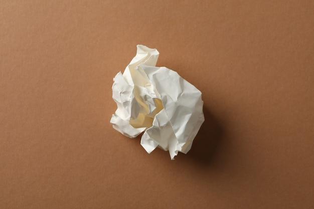 Papierkugel auf braunem hintergrund, platz für text