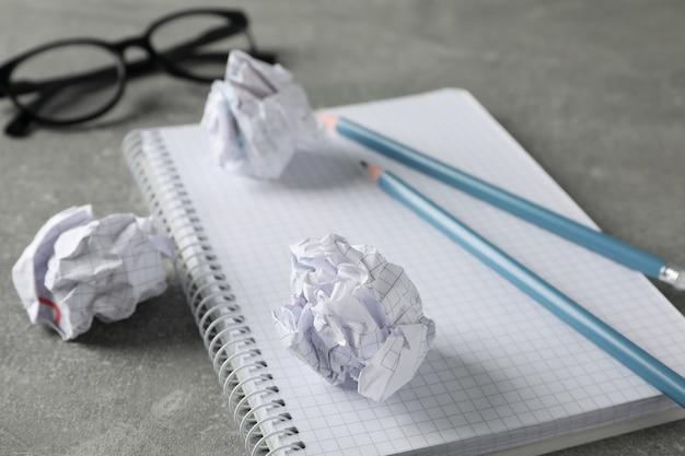 Papierkugeln, notizbuch, gläser und bleistifte auf grauem tisch, nahaufnahme