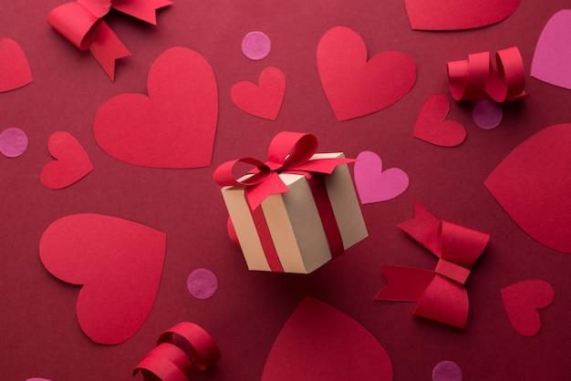 Papierkunst-valentinstagkonzept mit handgemachter geschenkbox, papierschnittband, schleife und vielen herzen