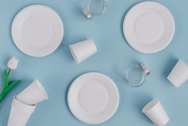 Papierlebensmittelverpackungen und -glaswaren von den umweltfreundlichen materialien auf hellblauem hintergrund.