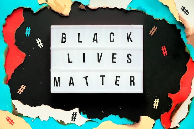 Papierloch mit verbrannten kanten, text black lives matter auf leuchtkasten, umgeben von hashtags