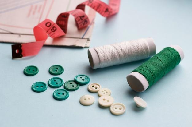 Papiermuster, -threads und -knöpfe auf einem blauen hintergrund