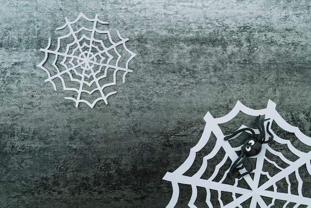 Papiernetz mit spielzeugspinne auf grauem hintergrund