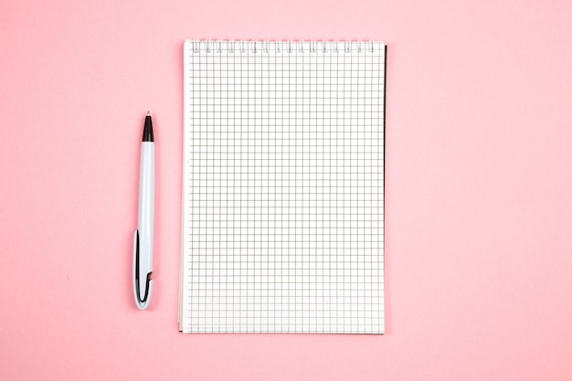 Papiernotizbuch mit stift auf rosa lokalisiertem hintergrund. ansicht von oben. flach liegen. attrappe, lehrmodell, simulation