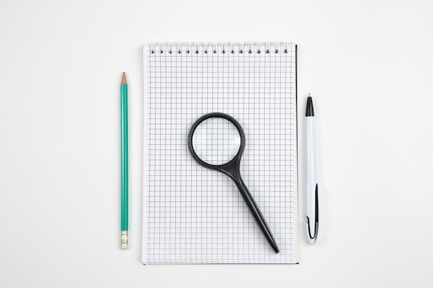 Papiernotizbuch mit stift oder bleistift auf weißem getrenntem hintergrund. ansicht von oben. flach liegen. attrappe, lehrmodell, simulation