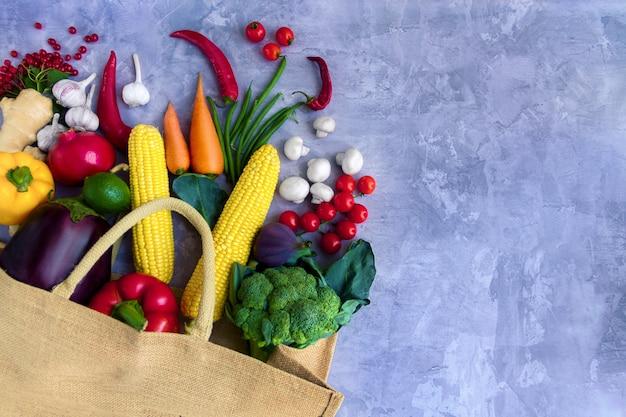 Papierpaket des veganen vegetariers mit frischem buntem leckerem rohem bio-rohkostgemüse und -früchten: kohl, brokkoli, pfeffer, karotte, tomate, champignon, chili lokalisiert auf grauem hintergrund