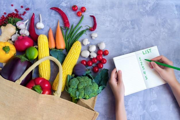 Papierpaket von veganem vegetarier mit frischem, buntem, leckerem, rohem, biologischem, rohem, gesundem gemüse und obst: kohl, brokkoli, pfeffer, karotte, tomate, champignon, chili als kaufliste auf dem markt