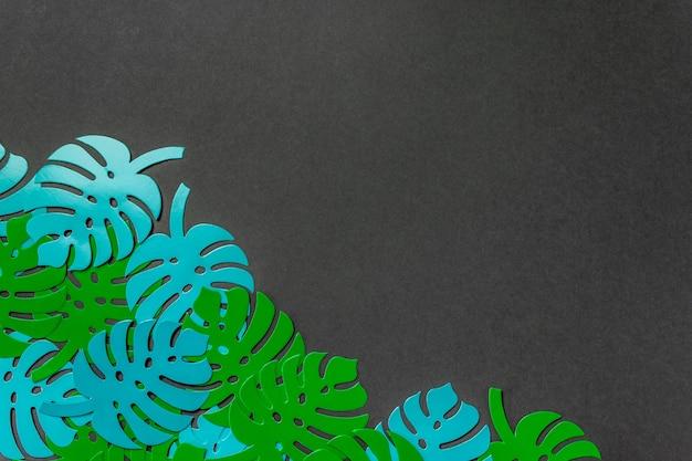 Papierpalmenblätter auf einem grünen hintergrund. minimales konzept. flach liegen.