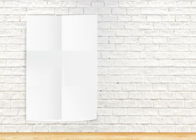 Papierplakat, welches die weiße backsteinmauer und den holzfußboden hängt