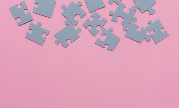 Papierpuzzles auf einem rosa