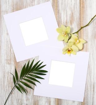 Papierrahmen mit gelben orchideen und palmblättern