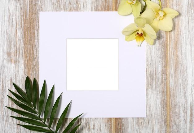 Papierrahmen mit gelber orchidee und palmblättern