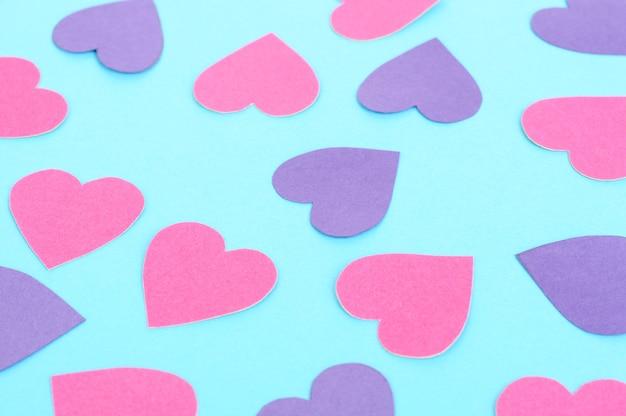Papierrosa und lila herzen auf blauem hintergrund