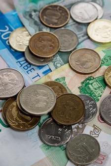 Papierrubel und münzen liegen auf einem haufen