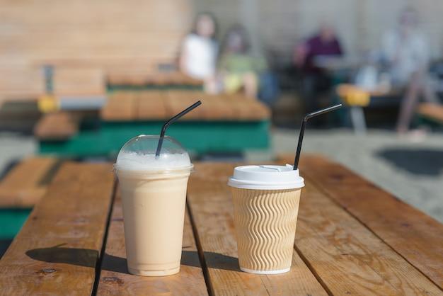 Papierschale mit heißem kaffee- und plastikglas mit eiskaffee auf holztisch im sommercafé. getränke, erfrischende getränke, kaffeethema.